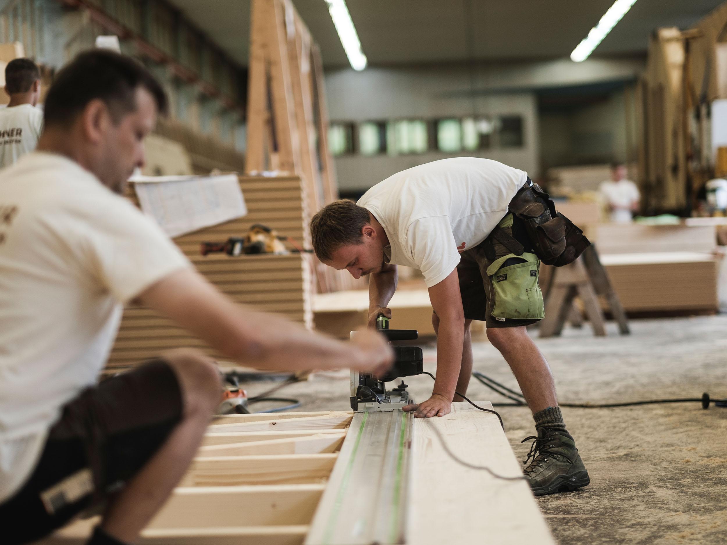 Buchner Holzbau Zimmerer bei der Arbeit Holz schneiden